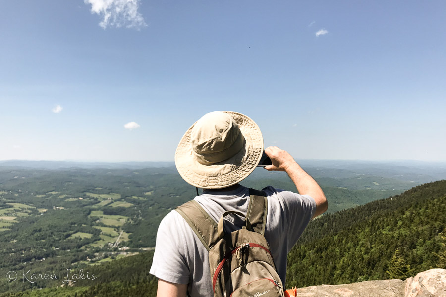 Greg taking a photo from a mountain vista
