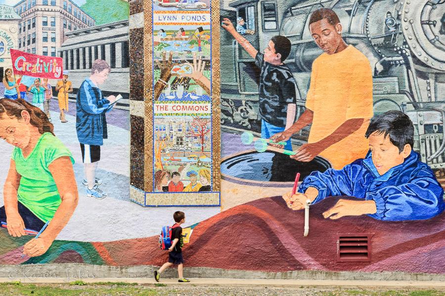 little boy in front of mural